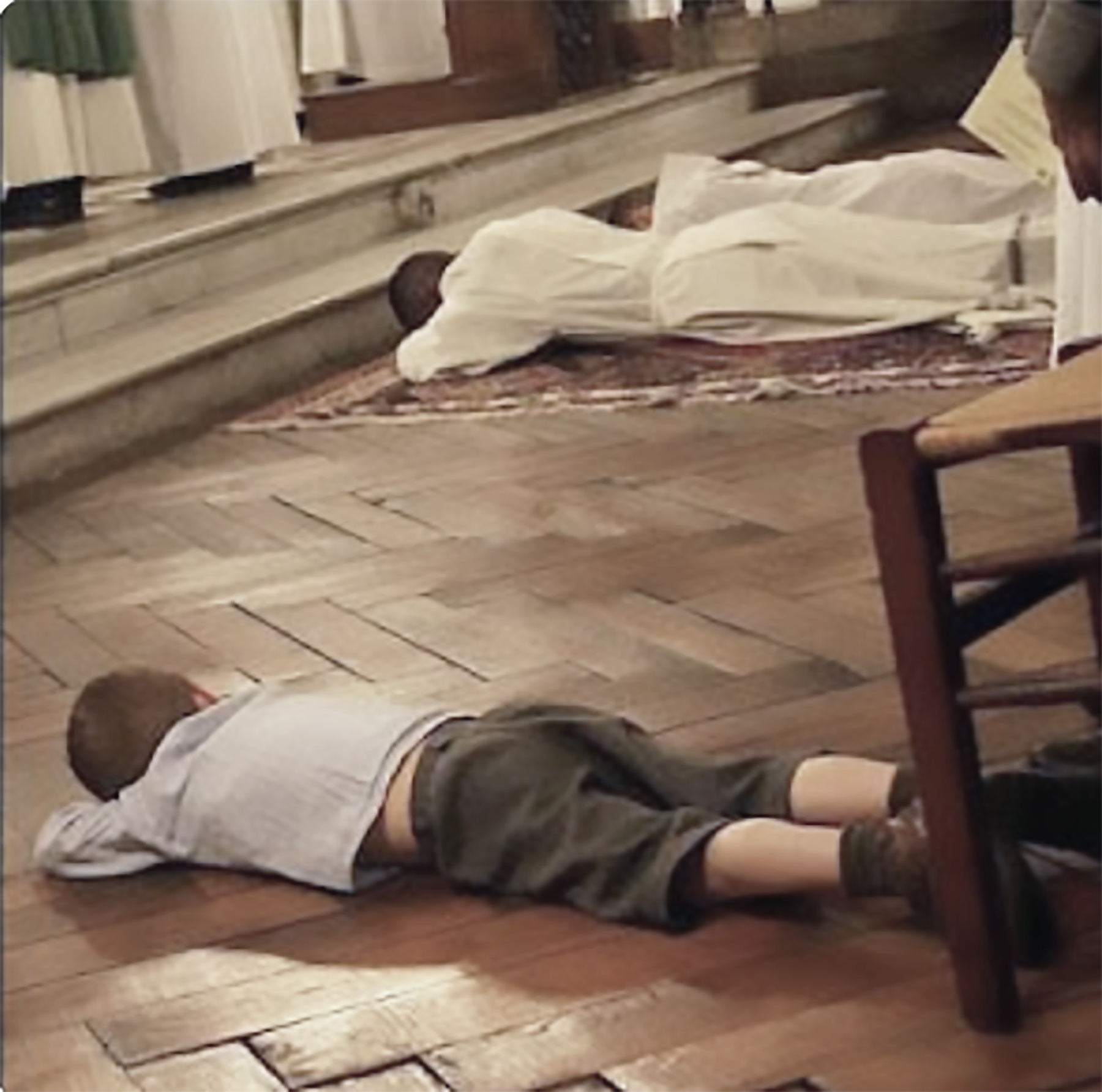 child laying down next to priest ordination